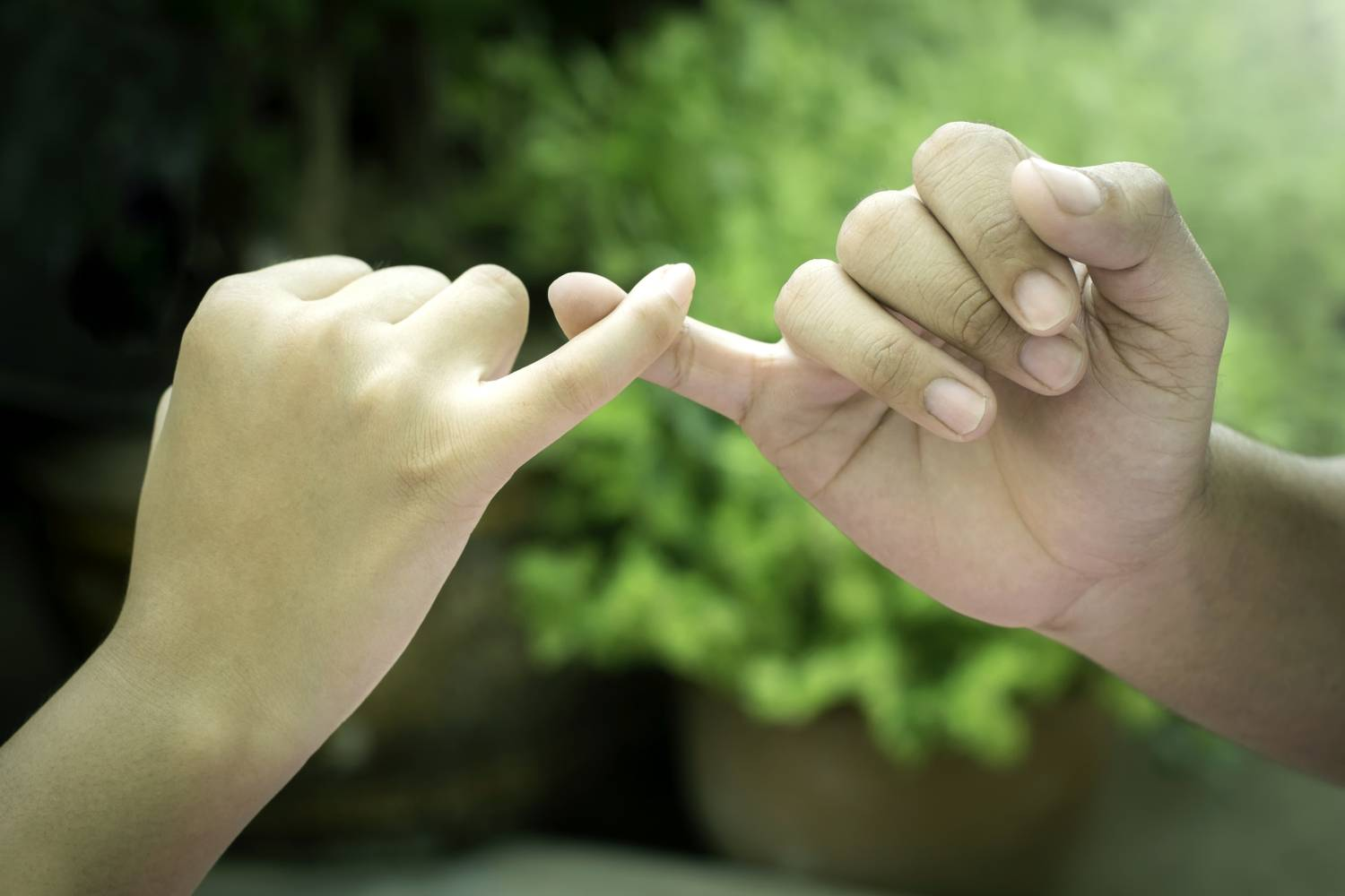image of two hands doing a pinky swear