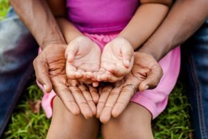 Hands of family together in green park - family unity and peace concept