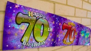 Happy 70th Birthday banner on wall