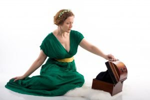 Lady in green antique dress opening box on white background