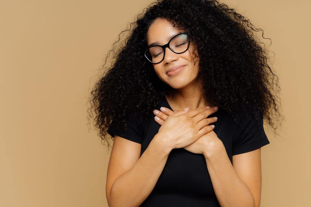 Touched lovely female with Afro hairstyle, keeps both palms on chest, has eyes shut from pleasure, hears heart piercing story, wears spectacles and casual t shirt, models against beige background