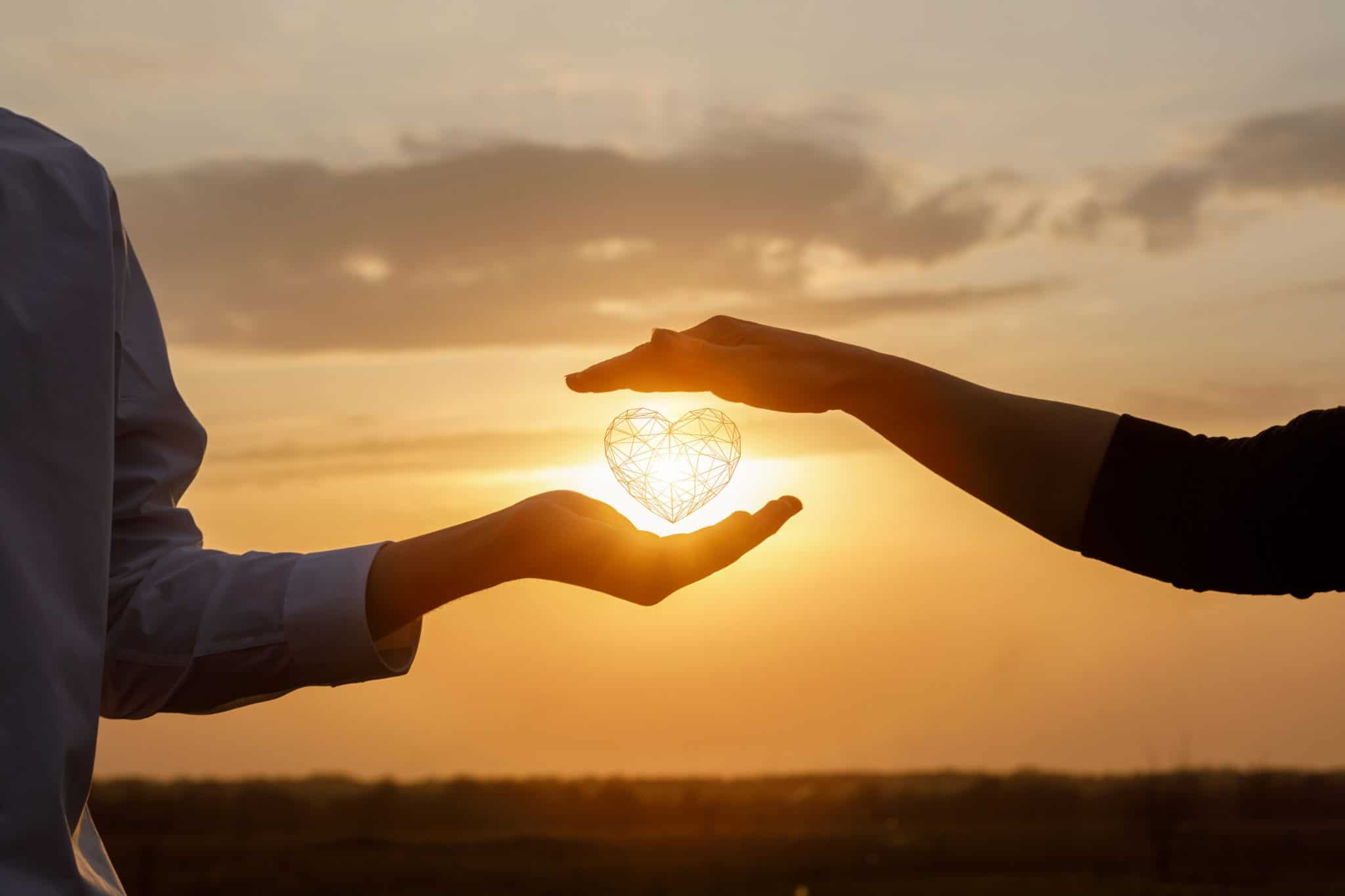 The concept of a love relationship between people. Hands interacts with a heart on a background of sunny sunset.