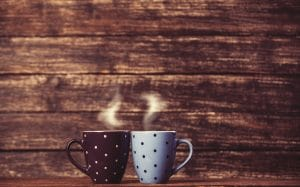 two tea or coffee cups on table, wood background