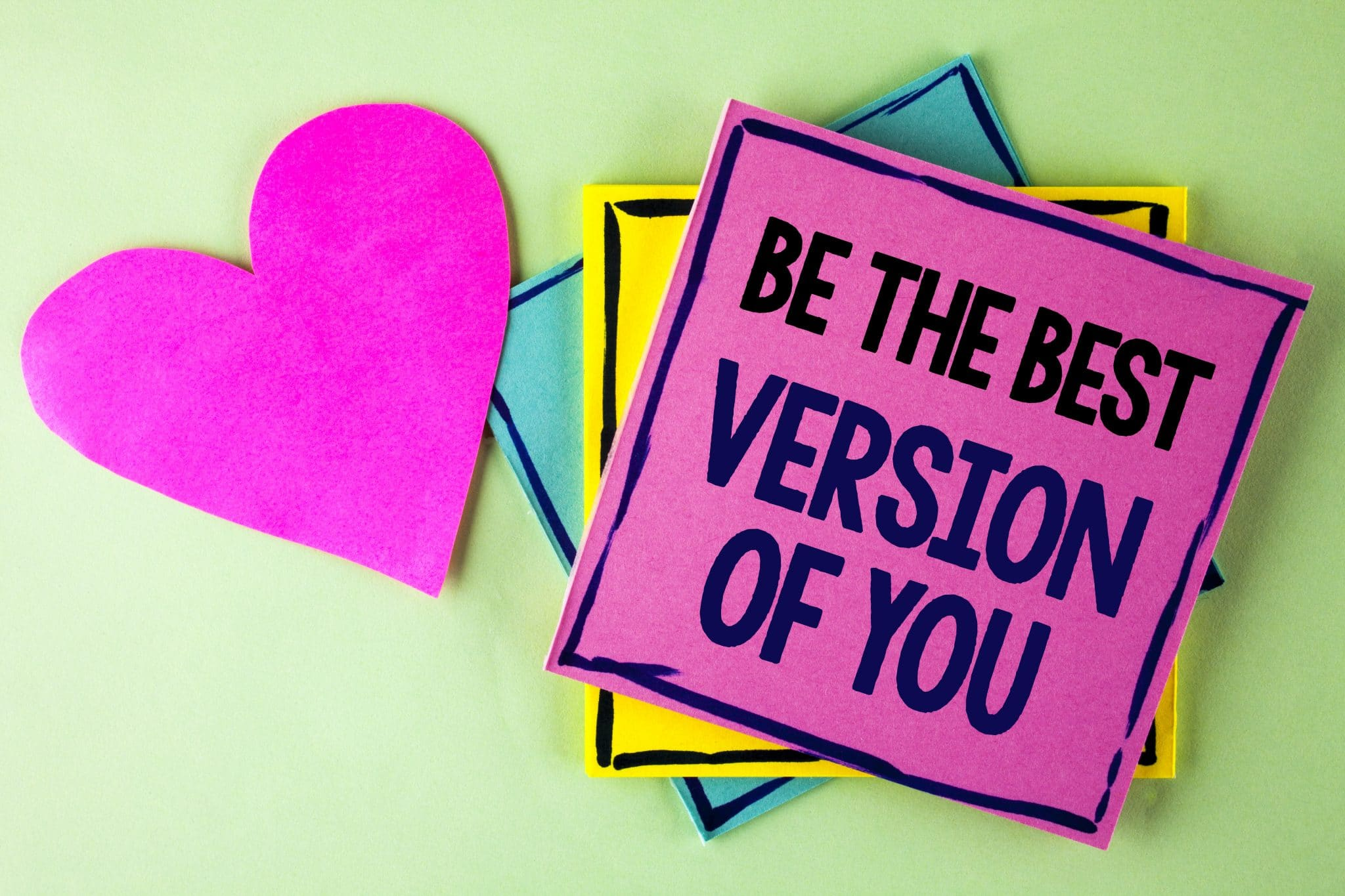 pink heart and blue, yellow, and pink notes stacked, top one says Be the best version of you.  Green background.