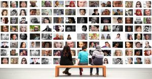 people sit on a bench in front of rectangles on wall of many faces